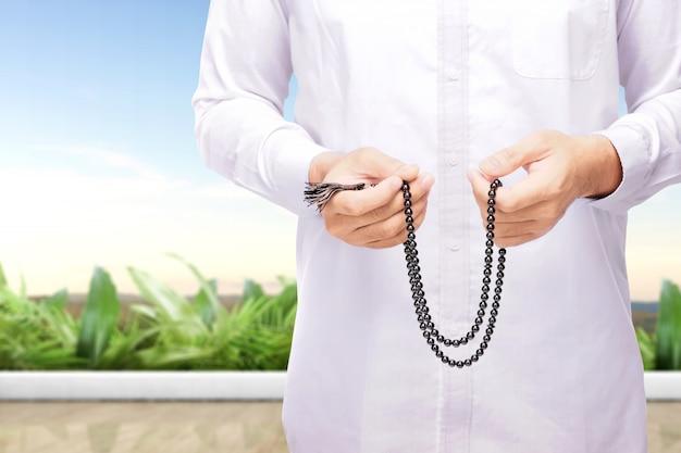 Muslimischer mann, der mit gebetsperlen auf seinen händen betet Premium Fotos