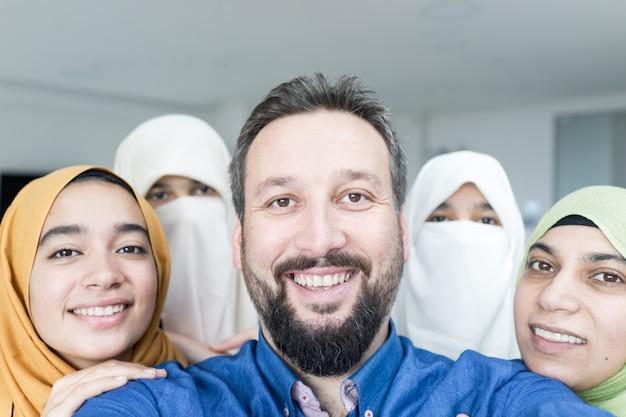 Muslimischer mann mit 4 frauenporträt Premium Fotos