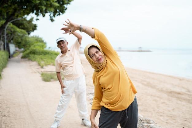 Muslimisches älteres paar, das sich im freien streckt und trainiert Premium Fotos