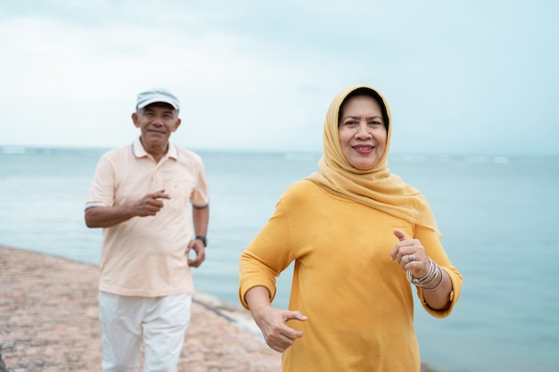 Muslimisches altes ehepaar trainieren und am strand laufen Premium Fotos
