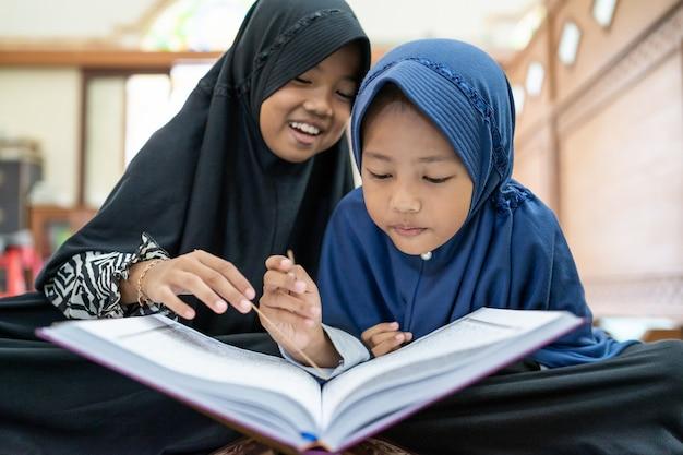 Muslimisches kind, das den koran liest Premium Fotos