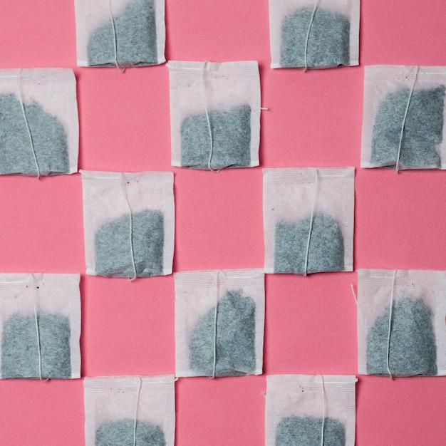 Muster des weißen teebeutels auf rosa hintergrund Kostenlose Fotos