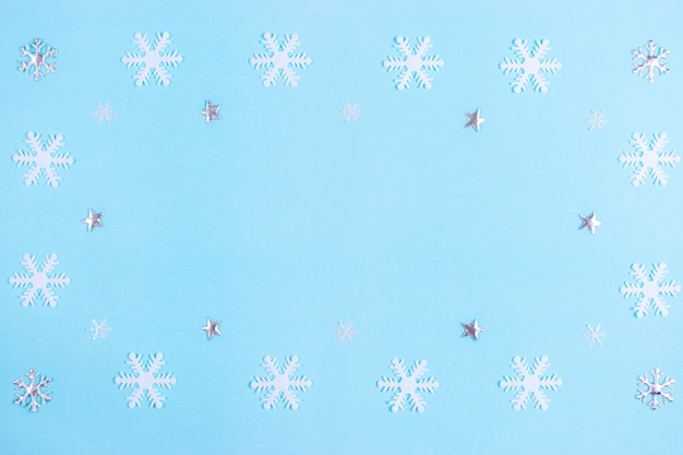 Muster gemacht vom silbernen stern und von den schneeflocken auf blauem pastellhintergrund. Premium Fotos