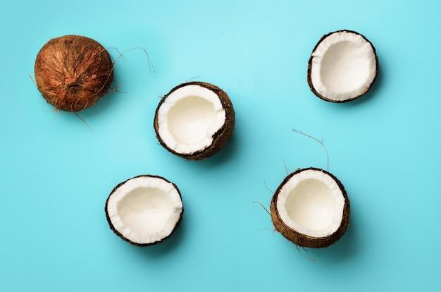 Muster mit reifen kokosnüssen auf blauem hintergrund. pop-art-design, kreatives sommerkonzept. die hälfte der kokosnuss in minimal flachem lay-style. Premium Fotos