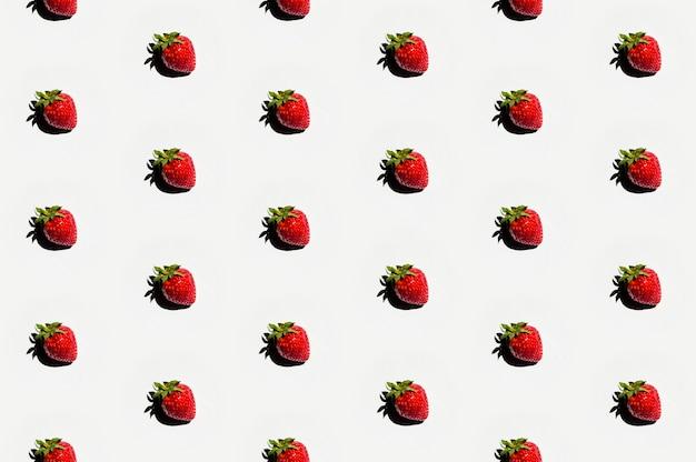 Muster von köstlichen erdbeeren auf weißer oberfläche Kostenlose Fotos