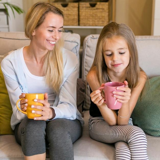 Mutter, die an ihrem kind lächelt und becher hält Kostenlose Fotos