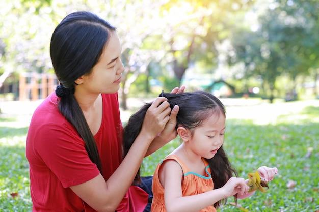 Mutter, die das haar der tochter kämmt, das im grünen garten liegt. Premium Fotos