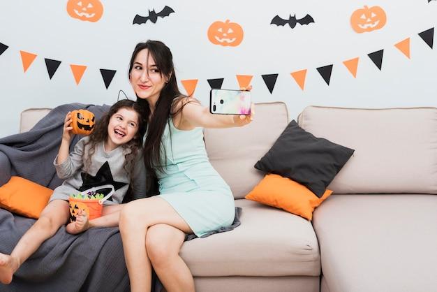 Mutter, die ein selfie mit tochter an halloween nimmt Kostenlose Fotos