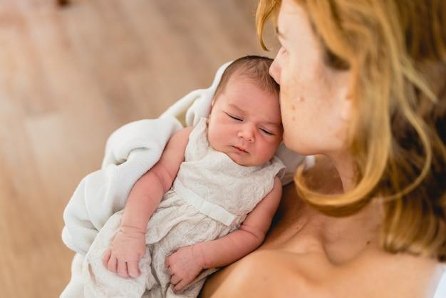 Mutter, die ihre neugeborene tochter nach dem stillen küsst Premium Fotos