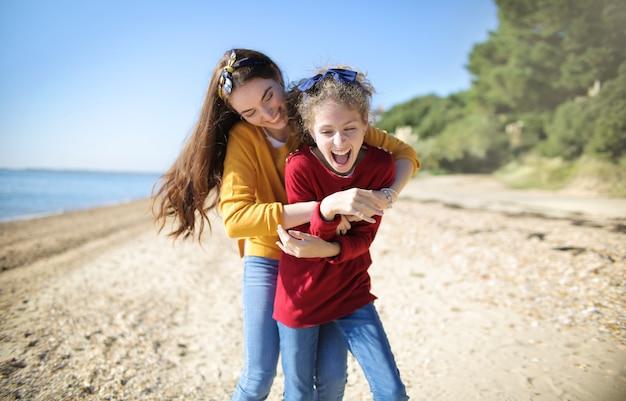 Mutter, die ihre tochter kitzelt und am strand spielt Premium Fotos