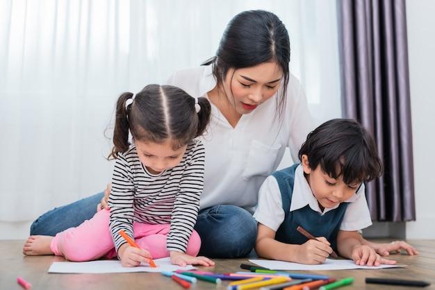 Mutter, die kinder in zeichenklasse unterrichtet. tochter- und sohnmalerei mit zeichenstiftfarbe herein Premium Fotos