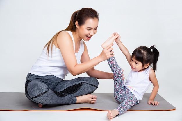 Mutter, die nette tochter unterrichtet, beinmuskeln auszudehnen. Kostenlose Fotos