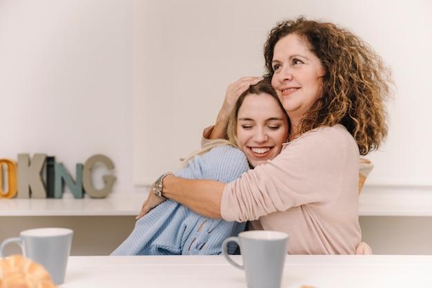 Mutter, die tochter während des frühstücks umarmt Kostenlose Fotos