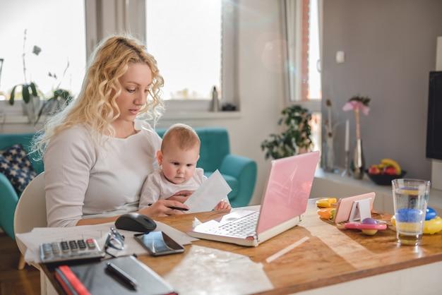 Mutter, die zu hause büro mit ihrem baby bearbeitet Premium Fotos