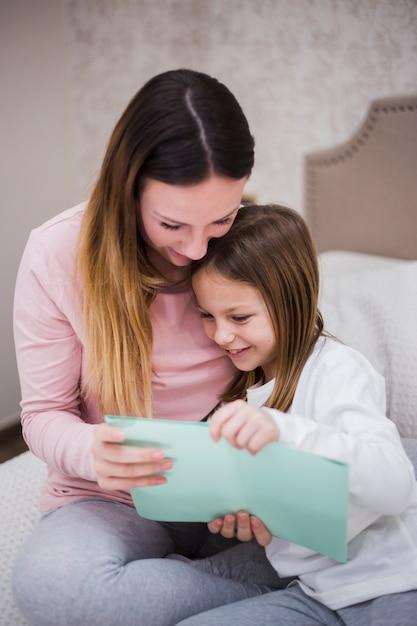Mutter, die zusammen mit tochter liest   Kostenlose Foto