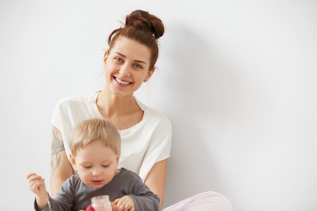 Mutter füttert ihren kleinen jungen mit löffel Kostenlose Fotos