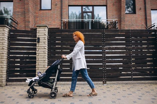 Mutter geht mit ihrem kleinen sohn im kinderwagen am haus vorbei Kostenlose Fotos