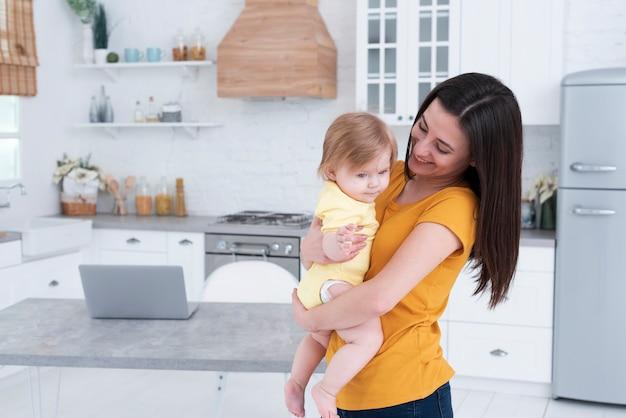 Mutter hält baby in der küche Kostenlose Fotos