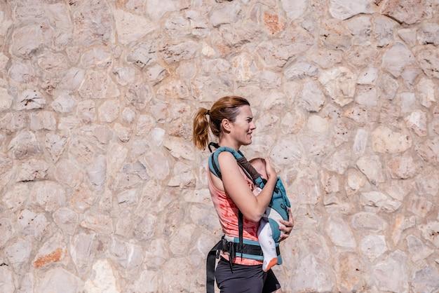 Mutter in der sportkleidung gehend ihr baby in ihrer babytrage. Premium Fotos