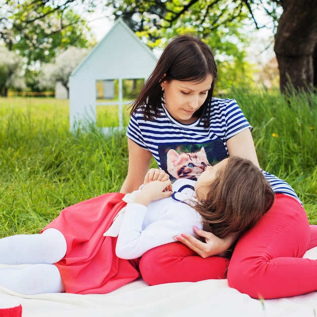 Mutter kommuniziert mit einer kleinen tochter im park. quadrat. das konzept von kindheit, familie, freundschaft, lebensstil. Premium Fotos