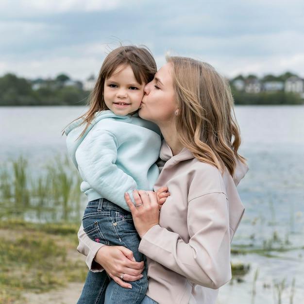 Mutter küsst ihre tochter vorderansicht | Kostenlose Foto