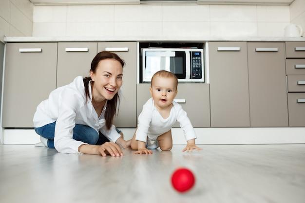 Mutter lächelt als baby, das auf boden kriecht, um ball zu bekommen Kostenlose Fotos