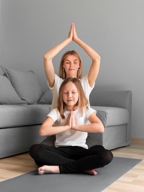 Mutter lehrt mädchen, yoga zu machen Premium Fotos