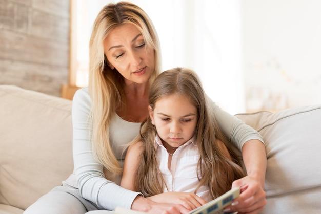 Mutter liest zu hause vom buch zur tochter Kostenlose Fotos