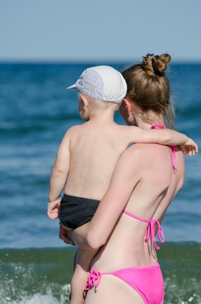 Mutter mit baby im badeanzug, der das meer betrachtet Premium Fotos