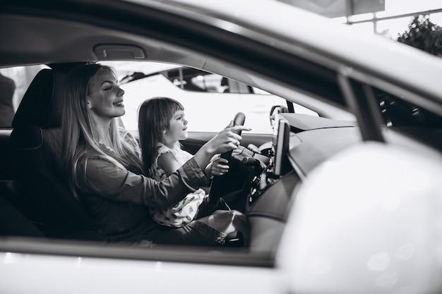 Mutter mit dem kleinen daughet, der in einem auto in einem autosalon sitzt Kostenlose Fotos