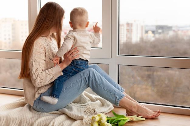 Mutter mit dem kleinen jungen, der auf fenster schaut Kostenlose Fotos