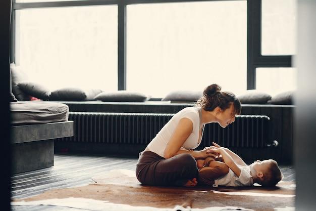 Mutter mit dem kleinen sohn, der zu hause yoga tut Kostenlose Fotos