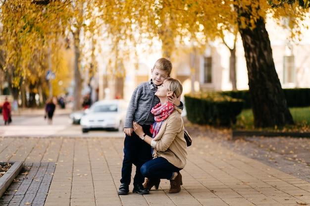 Mutter mit dem sohn, der im herbst im freien geht Kostenlose Fotos