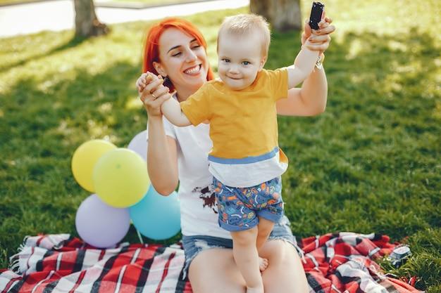 Mutter mit dem sohn, der in einem sommerpark spielt Kostenlose Fotos