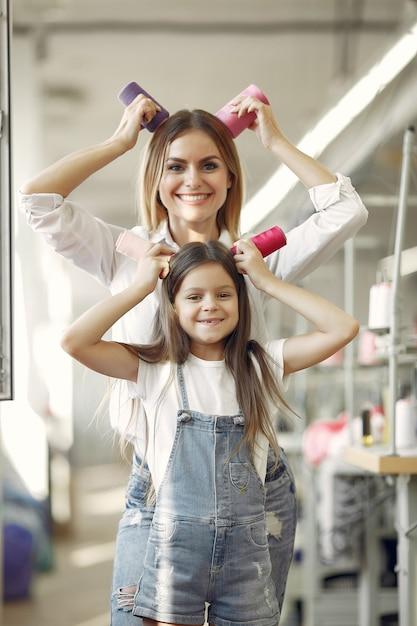 Mutter mit der kleinen tochter, die am gewebe mit thread steht Kostenlose Fotos
