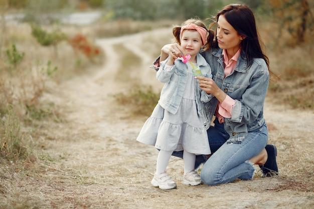 Mutter mit der kleinen tochter, die auf einem gebiet spielt Kostenlose Fotos