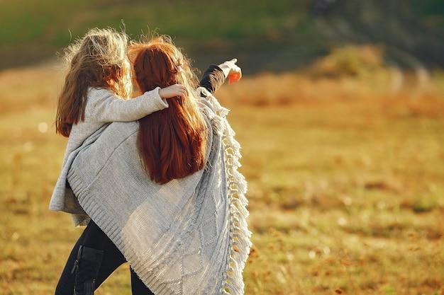 Mutter mit der kleinen tochter, die auf einem herbstgebiet spielt Kostenlose Fotos