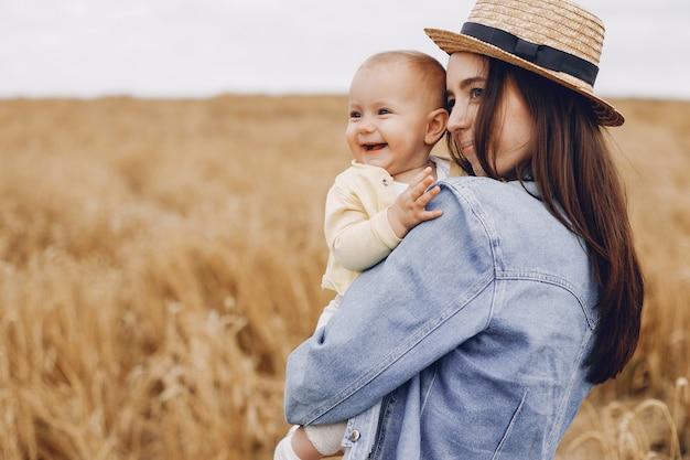 Mutter mit der tochter, die auf einem herbstgebiet spielt Kostenlose Fotos