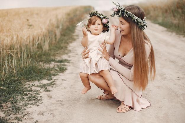 Mutter mit der tochter, die auf einem sommergebiet spielt Kostenlose Fotos