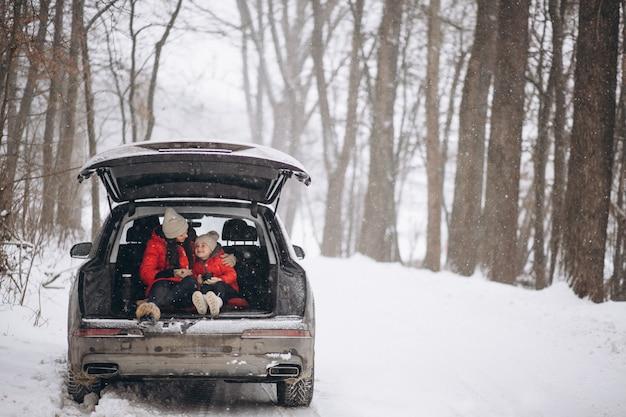 Mutter mit der tochter, die im auto im winter sitzt Kostenlose Fotos