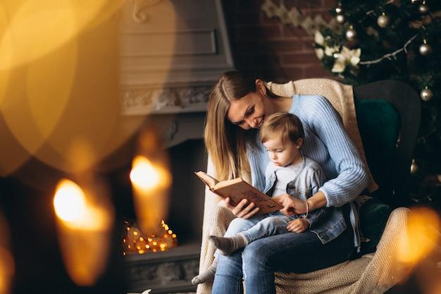 Mutter mit der tochter, die im stuhl durch weihnachtsbaum sitzt Kostenlose Fotos