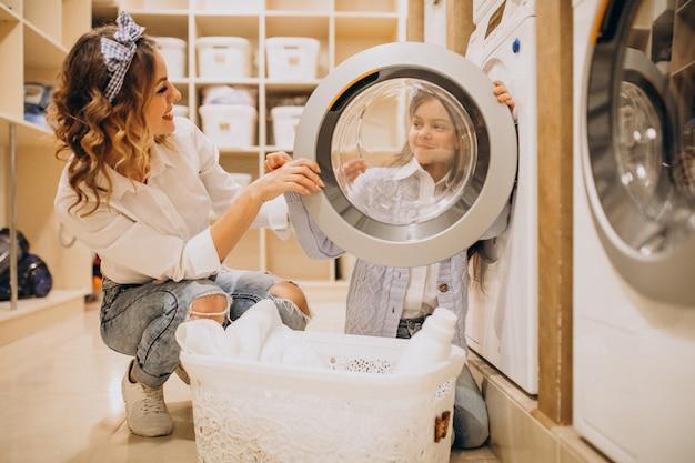 Mutter mit der tochter, die wäscherei am waschsalon der selbstbedienung tut Kostenlose Fotos