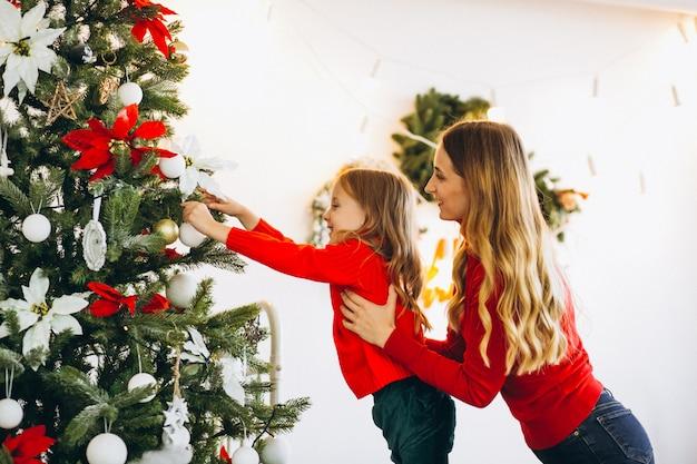 Mutter mit der tochter, die weihnachtsbaum verziert Kostenlose Fotos