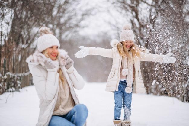 Mutter mit der tochter, die zusammen in einen winterpark geht Kostenlose Fotos