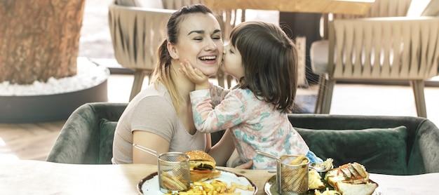 Mutter mit einer niedlichen tochter, die fast food in einem café isst Kostenlose Fotos