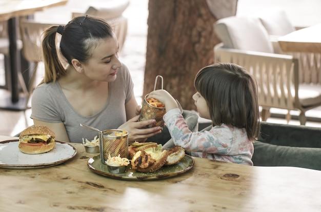 Mutter mit einer süßen tochter, die fast food in einem café isst Kostenlose Fotos
