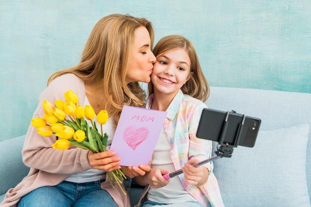 Mutter mit geschenken die tochter küssend, die selfie nimmt Kostenlose Fotos