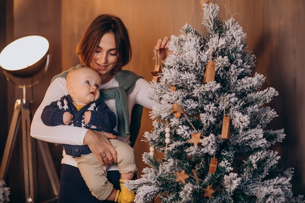Mutter mit ihrem baby, das weihnachten feiert Kostenlose Fotos