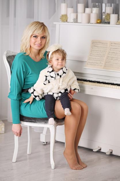 Mutter mit ihrem kleinen mädchen, das nahe einem klavier sitzt Premium Fotos