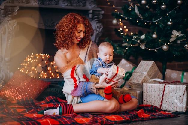 Mutter mit ihrem kleinen sohn am weihnachtsbaum mit geschenken Kostenlose Fotos